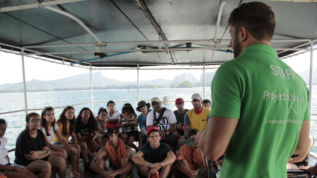 Personal local le explica procedimientos de seguridad a voluntarios en Tailandia.